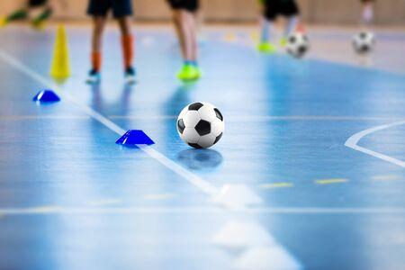 Futsal soccer training field. Young sports players with balls on training. Close up of futsal ball. Futsal Junior Player on Indoor Training. Soccer Winter Class at School Indoor Futsal Court 版權商用圖片