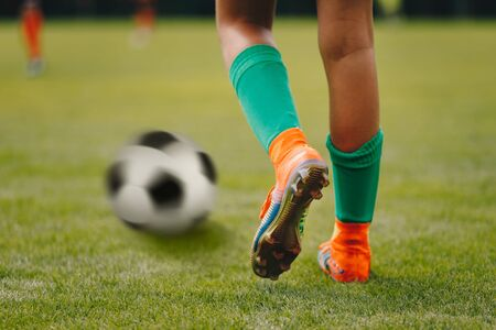 Single soccer football player standing next to ball ready to kick. Legs of senior level professional football player and classic soccer ball