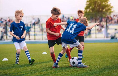 Kids Kicking Football Ball. Boys Play Soccer on Grass Field. Spectators Parents in the Background. Youth Players kicking Soccer Match on grass Stadium. Youth Football Tournament 版權商用圖片