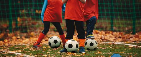 Three boys on soccer training in autumn time. Fall soccer outdoor practice session. Soccer players with ball on grass field covered with autumn leaves  版權商用圖片