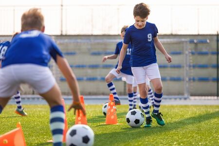 Youth Footballer Runing With Ball on Training Time. Boys Improving Soccer Skills on Training School Field. Physical Education Soccer Unit 版權商用圖片