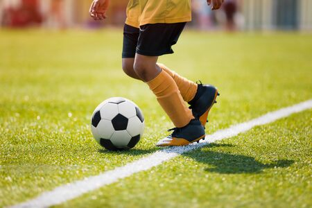 Junior afro american soccer player. Child running with soccer ball along side line of summer grass pitch