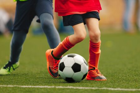 Close-up of child with soccer ball running on grass. Kids kicking football match in sports clothes