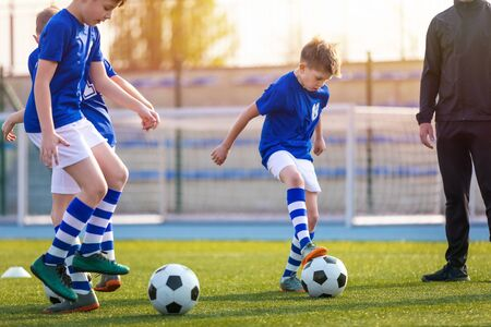 Kids Doing Sports Outdoor. Soccer Training for Children. Boys Training with Youth Coach. Summer Sunset Over Stadium Tribune in the Bacground. Kids Blue Sports Jersey Shirts 版權商用圖片