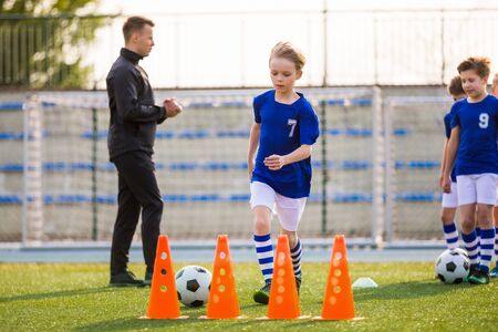 Young Happy Blonde Soccer Player Running with Ball on Training. Coach of Youth Football Team Explaining Drill Exercise in the Background. Caucasian Soccer Players on Practice Session