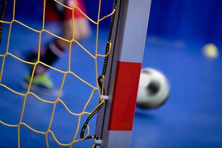 Indoor Soccer Background. Futsal Junior Player on Indoor Training. Soccer Goal with Yellow Net. Soccer Winter Class at School Indoor Futsal Court. Young Player in an Indoor Play-field 版權商用圖片
