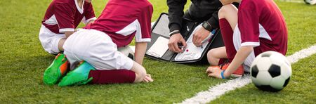 Coach coaching soccer kids soccer team. Youth sports coach using tactics board. Trainer explaining match strategy. Sports soccer education. Three junior players sitting with coach on grass pitch Banco de Imagens
