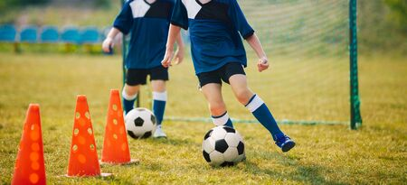 Exercises for football soccer youth team. Soccer football players during the team training before the match. Young player exercises with ball and marker cones