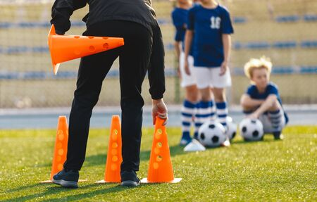 Soccer Coach Placing Training Cones for Kids Sports Team. Children on Soccer Football Class. Physical Education Soccer Unit Practice on Summer Sunny Day 版權商用圖片