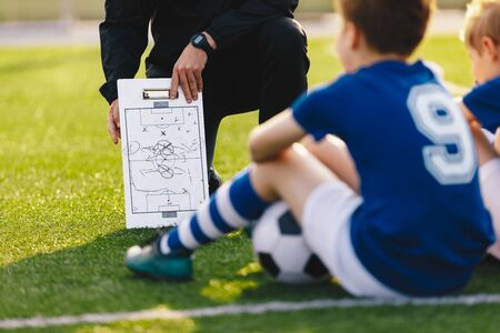 Soccer Team Meeting. Coach Giving Tactic Advices Using Football White Board. Coaching Youth Sports Team 版權商用圖片