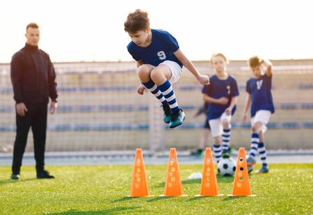 Soccer Training Unit. Boys Improving Soccer Drills and Skills. Young Coach Coaching  Kids on the Field. Boy Jumping High Over Training Cones. Agility Sports Practice Session