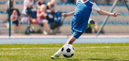 Football Soccer Kick. Young Player in Motion Kicking Soccer Ball on Soccer Field. Football Stadium and Spectators in the Background