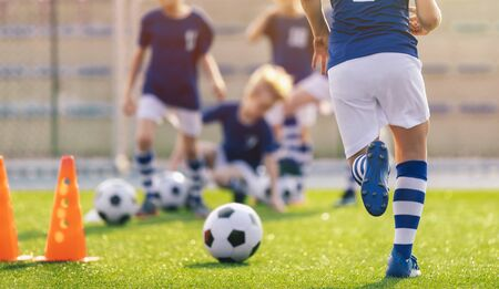 Soccer training practice. Player running with football ball in sports grass cleats. Training session in soccer for youth players. Kids on school sports venue