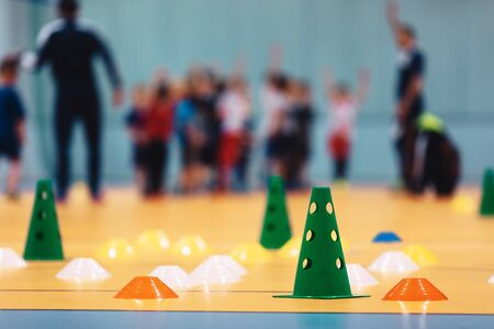 Indoor soccer training during the winter. Futsal practice for children. Kids with futsal coach. Physical education unit of soccer. Futsal training field with colourful equipment, cones and markers