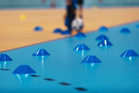 Indoor soccer training during the winter. Futsal training field with blue cones. Indoor football practice for children. Physical education unit of soccer