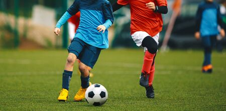 Youth Football Tournament. Youth Players Kicking Soccer Match on grass Stadium. Two Junior Level Soccer Players in Red and Blue Shirts Compete for Ball 版權商用圖片