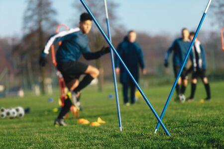 Football soccer training session for junior level athletes. Boys football training session. Youth players running slalom, jumping and kicking soccer balls. Young boys improving soccer skills 版權商用圖片