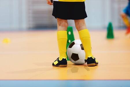 Football futsal training for children. Indoor soccer young player with a soccer ball in a sports hall. Soccer training dribbling cone drill. Player in blue uniform. Sport background.