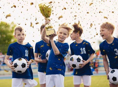 Happy kids in elementary school sports team celebrating soccer succes in tournament final game. Boys smiling and rising up golden cup on trophy ceremony