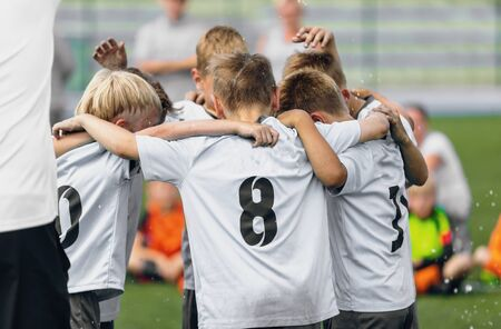 Happy kids in sports team dancing and celebrating school championship. Boys huddling in team outdoor in sunny summer day