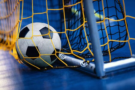 Indoor Soccer Futsal Ball On Goal With Net And Blue Background. Indoor Football Background