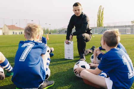 Young Coach Explaining Soccer Positions and Match Tactics to Youth. Kids Football Team Coaching. Children on Soccer Training