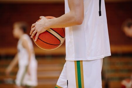 Junior basketball player on game. Youth basketball league background