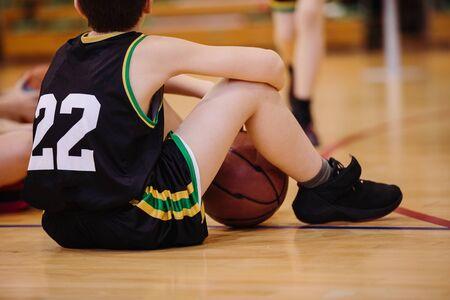 Junior basketball player sitting on the floor in backetball court 版權商用圖片