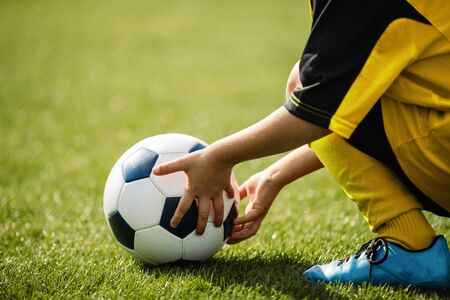 Child playing with soccer ball on grass venue. Little kid holding in both hands football ball. Young soccer player in blue cleats