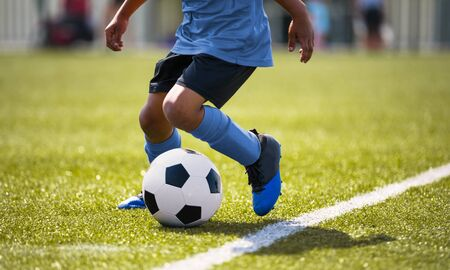 African American young boy playing soccer in a stadium pitch. Child running with soccer ball along the field white sideline. Junior soccer background Stockfoto