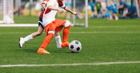 Boy Kicking Soccer Ball. Running Soccer Football Players. Five Junior Footballers on Duel. Football Grass Field and Soccer Stadium in the Background.