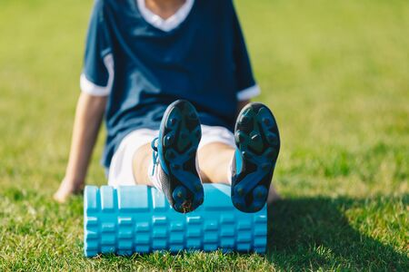 Foam Rolling. Young Soccer Player in Soccer Cleats Using Training Foam Roller