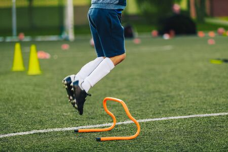 Soccer Player Jumping on Training Session Pitch. Football Training Equipment. Athlete Jumping Over Hurdle on Grass Field