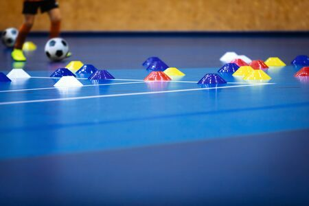 Indoor soccer player on training during the winter. Futsal training field with blue cones. Indoor football practice for children. Physical education unit of soccer at school