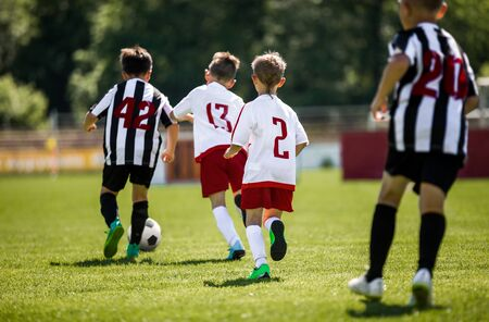 Young Boys In Football Teams Running in Duel After Soccer Ball