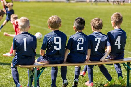 Friends on a Soccer Team Sitting on a Wooden Bench. Group of Interracial  Kids in a School Sports Team 版權商用圖片
