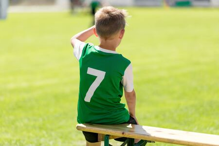 Soccer boy in grean jersey shirt sitting on wooden bench