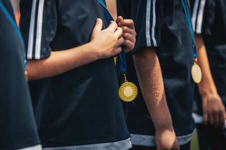 Sports kids players with golden medals standing in a row during celebration. Medals hanging around young sport players necks 版權商用圖片