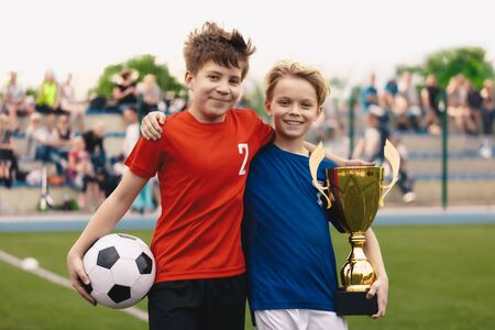 Happy two young boys as a soccer players hanging out on grass field. Kids with soccer ball and golden cup trophy. Children soccer team players smiling. Football friends from opposite teams before game 版權商用圖片