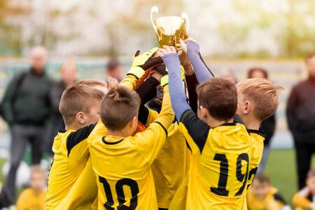 Happy kids in yellow shirts in elementary school sports team celebrating soccer succes in tournament final game. Sports team members raising golden cup trophy
