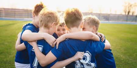 Happy kids in elementary school sports team celebrating soccer succes in tournament final game. Children soccer team team gathering together in a circle, to strategize, motivate and celebrate Stock Photo