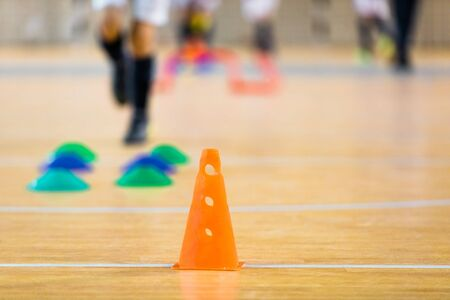 Indoor soccer futsal training field. Athletes training soccer indoor during winter time. Orange soccer cone and colorful markers on wooden floor