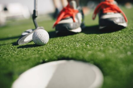 Kids play mini golf. Close-up image of player in snickers with mini golf club and white golf ball. e cup in the foregroundGold hole th