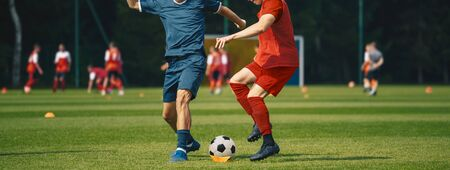 Two Men Kicking Soccer Ball. Junior Teenage Soccer Team on Training Game.  Athletes Running with Ball on Football Pitch. Young Soccer Players in Action 版權商用圖片
