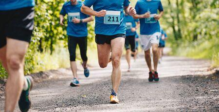 Group of runners running fast through the forest on trail marathon run 版權商用圖片