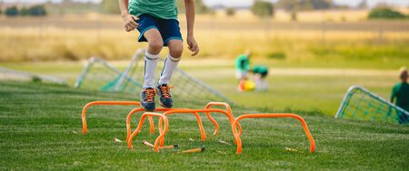 Low section portrait of unrecognizable boy jumping over hurdles in football field. Kid young athletes training with football equipment. Soccer speed durability training 版權商用圖片