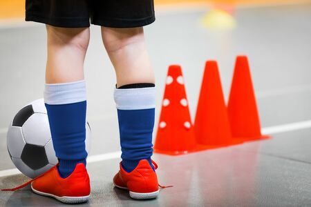 Children playing football in school gymnasium. Indoor soccer - futsal training for school kids. Football futsal player, ball, futsal floor and training cones