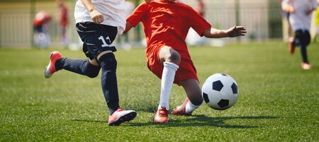 Sports players in football duel run. Footballers running fast and kicking soccer ball on grass stadium during school tournament match. Competition between defender and forward football players 版權商用圖片
