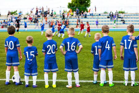 Équipe sportive pour enfants de niveau junior. Football Soccer Enfants Joueurs debout avec l'entraîneur pendant le match de compétition de football à l'école. Garçons en maillot de football bleu Sportswear et crampons de football