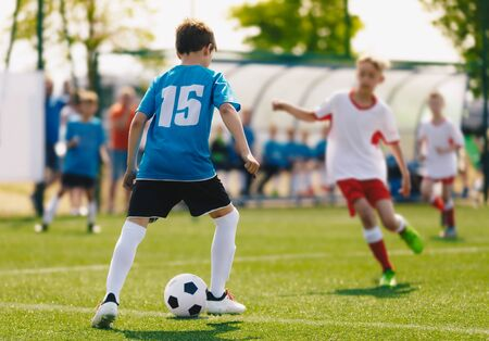School Soccer Boys Playing Tournament Match. Children Play Outdoor Sport on a Sunny Day. Junior Level Soccer Players Compete on Sports Grass Field. Bench and Substitute Players in Blurred Background